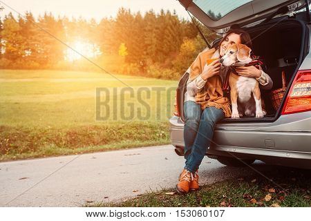 Woman with dog sits in car trunk on autumn road