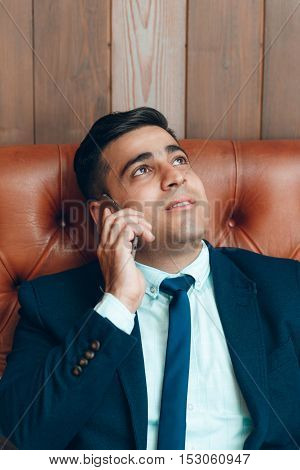Happy man talking on the smartphone, copy space for text on wooden wall. Cheerful businessman with dreaming look have private talk. Positive events. Receiving good news.