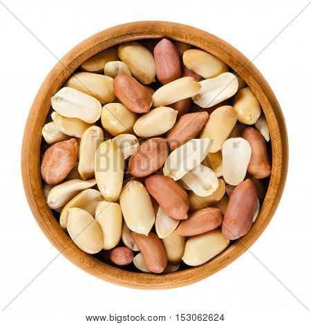 Shelled peanuts in wooden bowl on white background. Dry roasted Arachis hypogaea, also called groundnut and goober, used as a snack. Isolated macro food photo close up from above.