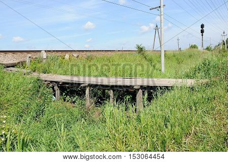 old wooden pedestrian bridge through a ditch to the railroad