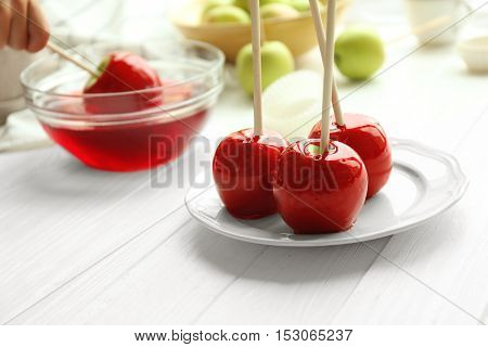 Testy red caramel apples on white plate