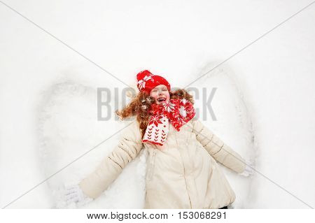 Laughing girl laying on a snow moving her hand up and down playing games winter outdoors. Little girl on a snow showing angel figures.