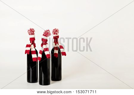 Merry Christmas and happy New year. Three bottles of wine in knitted caps and scarfs in red and white stripes on a white background. Selective focus.