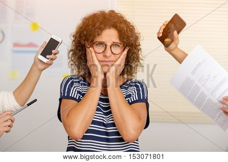 Creative concept of a ver busy middle age woman at the office full of work