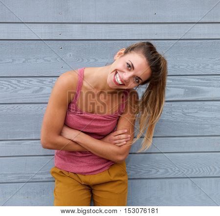 Smiling Woman With Hair In Ponytail And Arms Crossed