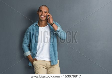 Young handsome man talking over phone and looking at camera. Young man leaning against grey wall. Portrait of happy casual african guy talking on the smartphone on grey background with copy space.