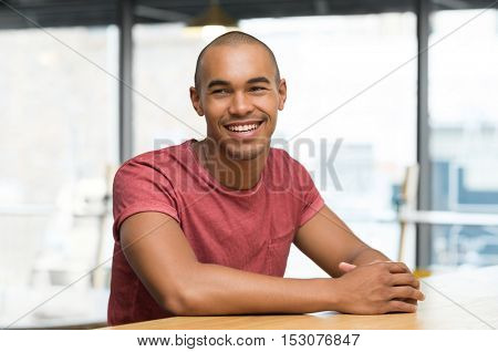Young man thinking while sitting on the chair at cafeteria. Portrait of african guy in casual day dreaming. Cheerful young man smiling while looking away sitting on chair.