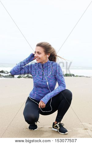 Sporty Woman Crouching On Beach Listening To Music