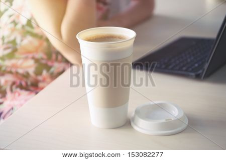 Coffee-to-go. Opened paper cup of coffee on table