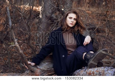 Fashion style portrait of young beautiful woman in black casual coat. Beautiful sad girl in autumn clothes outdoor. Autumn fashion woman wearing trendy coat. Fashion portrait of beautiful stylish brunette woman outdoors