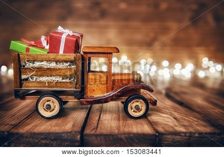 Merry Christmas and Happy Holidays! Gifts boxes presents on toy car and Christmas garland lights on old dark wooden rustic background. Celebration concept.