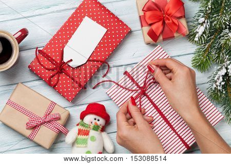 Female hands wrapping christmas gift box above wooden table. Top view with copy space