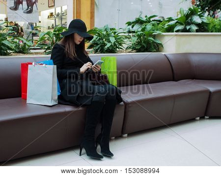 Beautiful elegant woman in a coat and hat with shopping bags and mobile phone. Shopping center