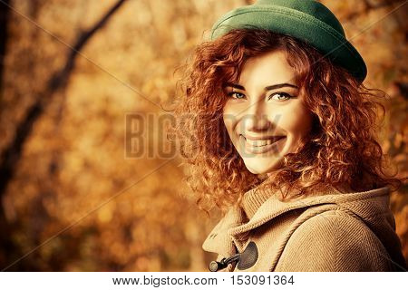 Smiling red haired girl enjoys a sunny autumn day. The mood of autumn, leaf fall. Autumn fashion.