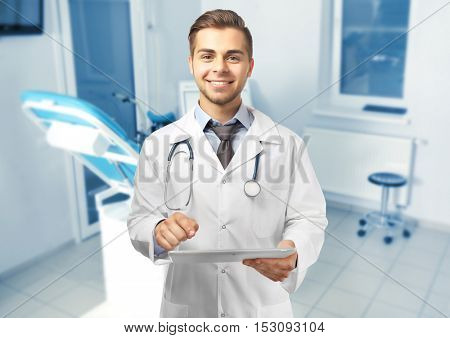 Professional male doctor with tablet on blurred consulting room background. Gynecology concept.