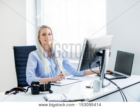 Digital artist at work. Young and attractive woman working in office. Retoucher editing photos. Blank monitor with copy space. Copyspace display.