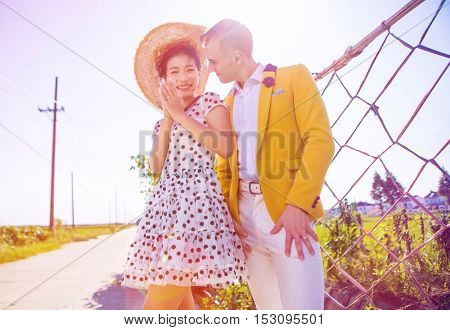 Attractive multi ethnic inter racial chinese and british couple standing in the road by the countryside wearing very stylish clothes