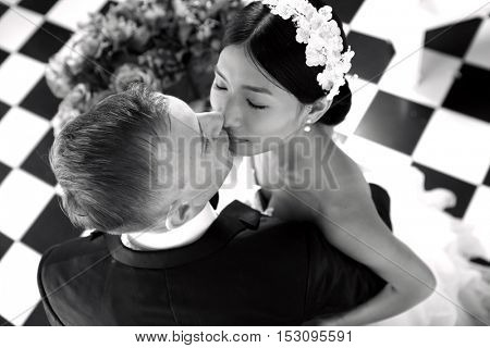 gorgeous stylish happy bride and groom performing their emotional first dance and having a romantic kiss