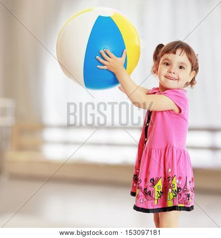 Happy little girl with pigtails on the head , in a pink dress. The girl lifted a large, inflatable striped ball.On the background of the great hall of the kindergarten with a semicircular window.