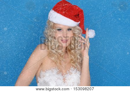 Smiling woman in Santa hat and snow on blue background