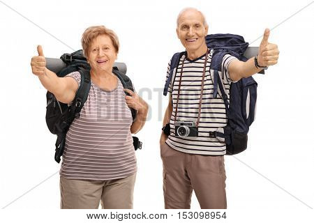 Cheerful senior hikers giving a thumb up isolated on white background