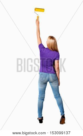 Back view of a girl who paints the paint roller. rear view people collection. backside view of person. Isolated over white background. Long-haired blonde in the purple shirt paints the wall roller