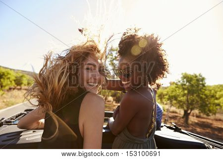 Two women standing in the back of open car turning to camera