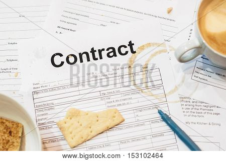 Dirty contract papers with cracker and coffee trace. Close-up of business documents of busy and tired businessman. Mess concept