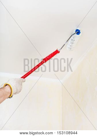 Worker Paints The Ceiling With White Paint