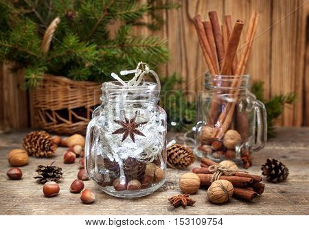 Christmas composition. Winter spices and ingredients for cooking the Christmas meal. Cinnamon sticks hazelnuts walnuts anise stars Christmas tree branches on old wooden background