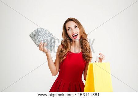 Portrait of a happy woman in red dress holding shopping bag and money isolated on a white background