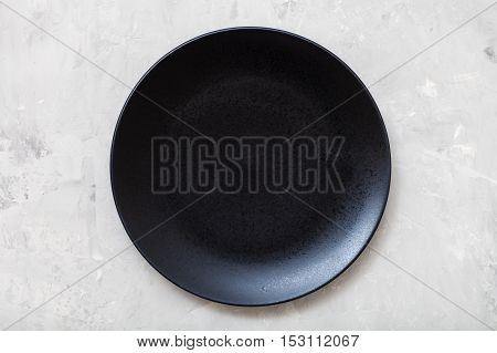 Above View Of Black Plate On Gray Concrete Surface