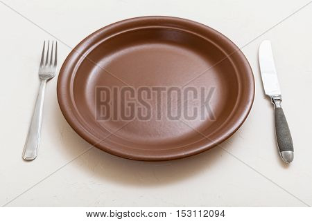 Brown Plate With Knife, Spoon On White Plaster