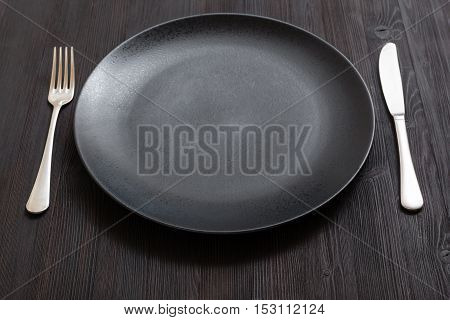 Black Plate With Knife, Spoon On Dark Brown Table