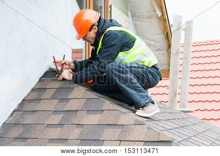 Roofer builder worker dismantling roof shingles .