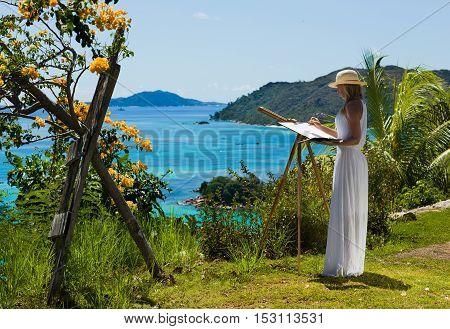 Beautiful, slim woman in white dress paints tropical landscape, sea