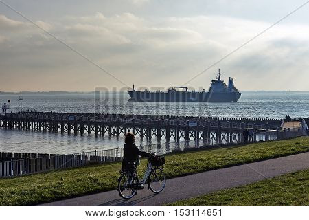 Freight Ship Entering Port Of Vlissingem Against Backlight