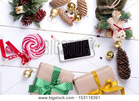 Smart phone mock up with rustic Christmas decorations for app presentation.cones. gifts. toys. View from top
