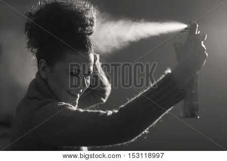 Black and white studio shot of a young girl spraying hairspray and fixing her haircut