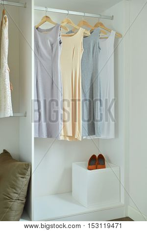 Female clothes on hangers in white wardrobe