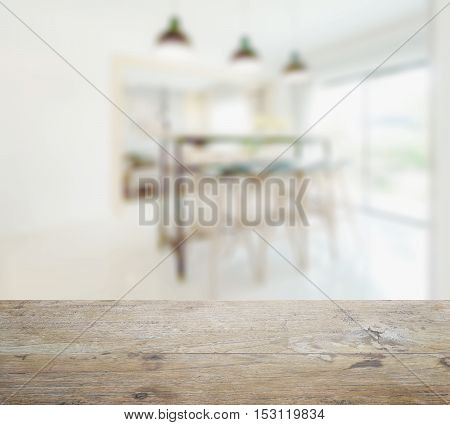 wooden table top with blur of modern dining table in dining room