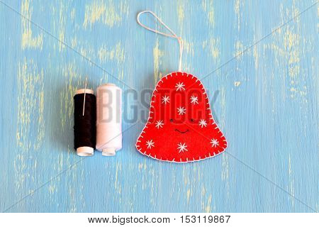 How to sew a Christmas felt bell ornament. Step. Fun felt Christmas bell ornament, white and black threads on a blue wooden background. Home decor idea for children. Easy felt sewing diy. Top view