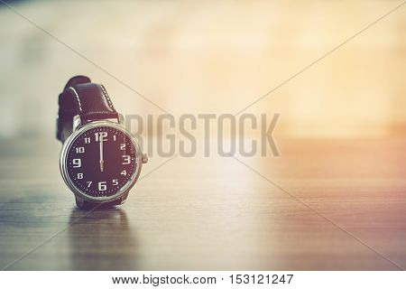 wristwatch on the table with blur bedroom background the time show midday or midnight