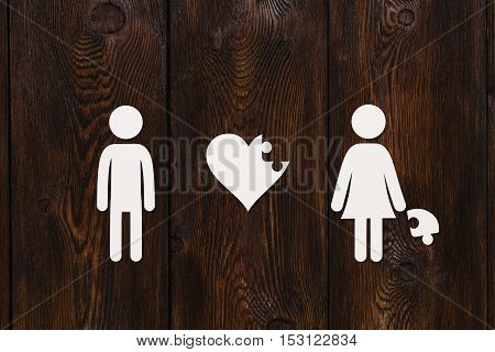 Paper man, woman and puzzle heart on dark wooden background. Love, relation concept. Abstract conceptual image