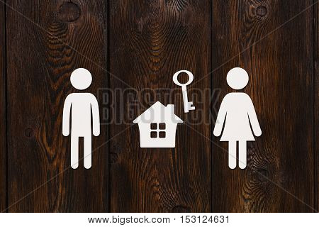 Paper man, woman and house with key on dark wooden background. Housing, family concept. Abstract conceptual image