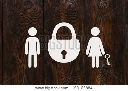 Paper man, woman with key and padlock on dark wooden background. Love relation concept. Abstract conceptual image