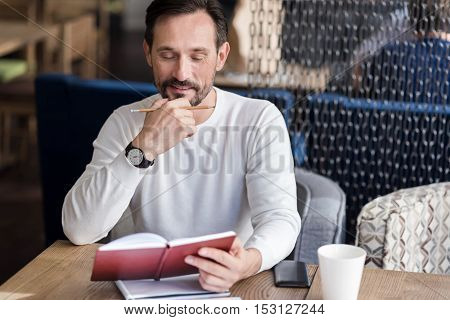 Lots to do. Handsome bearded man reading his notes though and holding his fingers on chin while sitting in cafe.