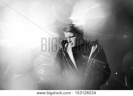 Black and white artistic photography. Young blonde man in black wear standing on street.