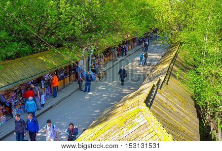 MOSCOW RUSSIA - MAY 10 2015: The shady street and wooden roofs of the covered galleries of the flea market in Izmailovo on May 10 in Moscow.