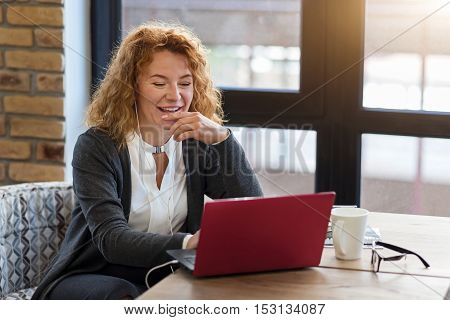 Skype conversation. Smiling red-haired woman using small modern laptop and holding her hand at her chin while sitting in cafe.